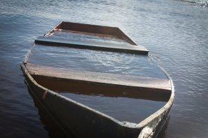 een bootje dat vol met water staat. Het zinkt nog net niet.