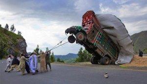groepje mensen probeert al touwtrekkend een vrachtwagen weer op vier wielen te krijgen