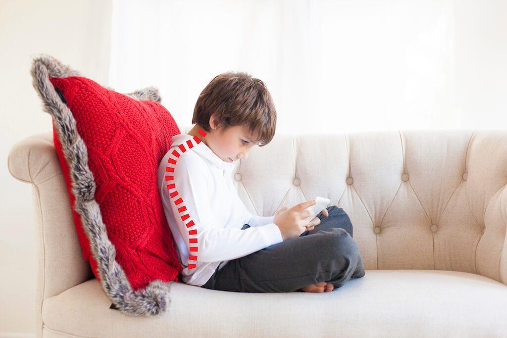 jongen zit met mobiel op de bank. Zijn hoofd leunt naar voren. De stand van de ruggegraat is als illustratie erbij getekend.