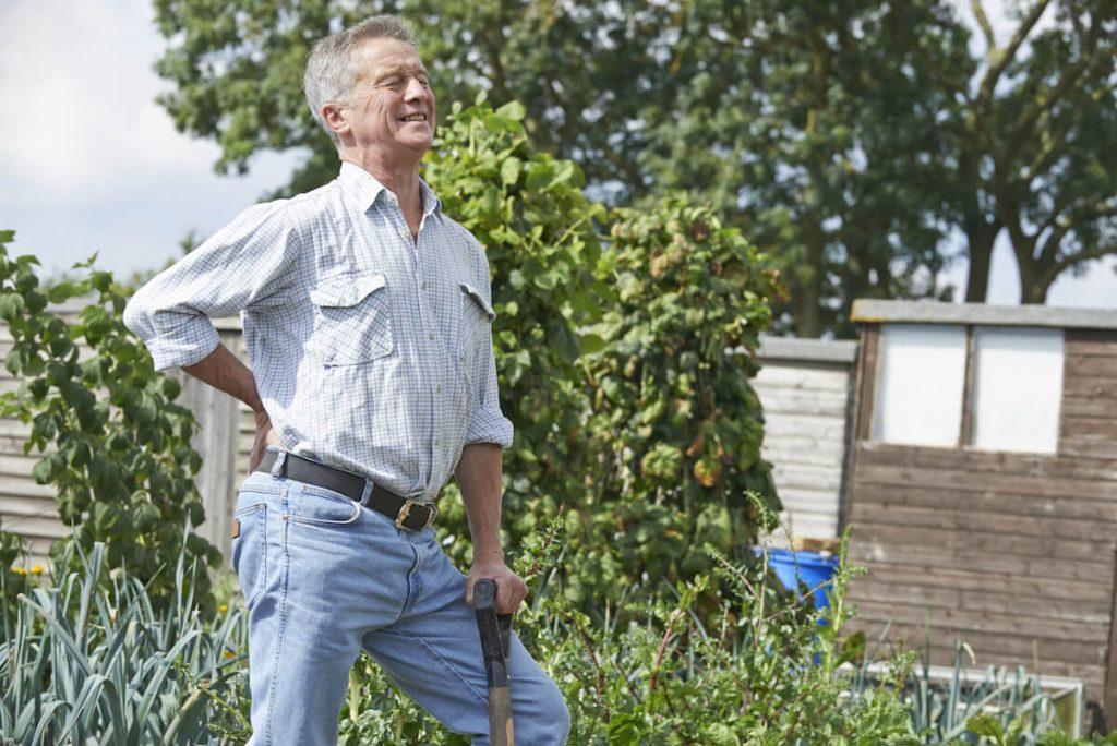 man aan het spitten in de tuin.