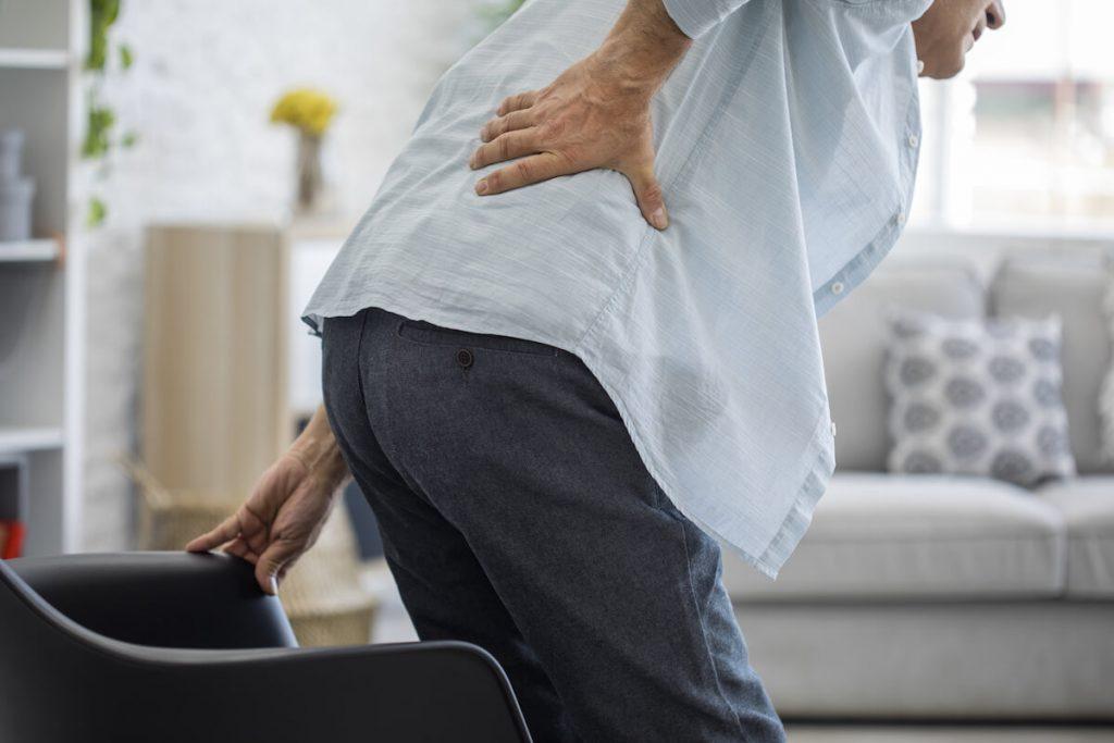 oudere man grijpt naar zijn onderrug