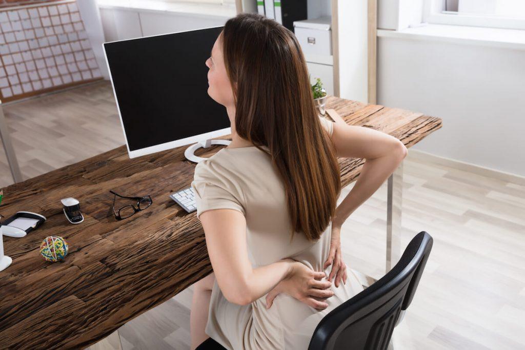 vrouw achter bureau heeft last van haar onderrug
